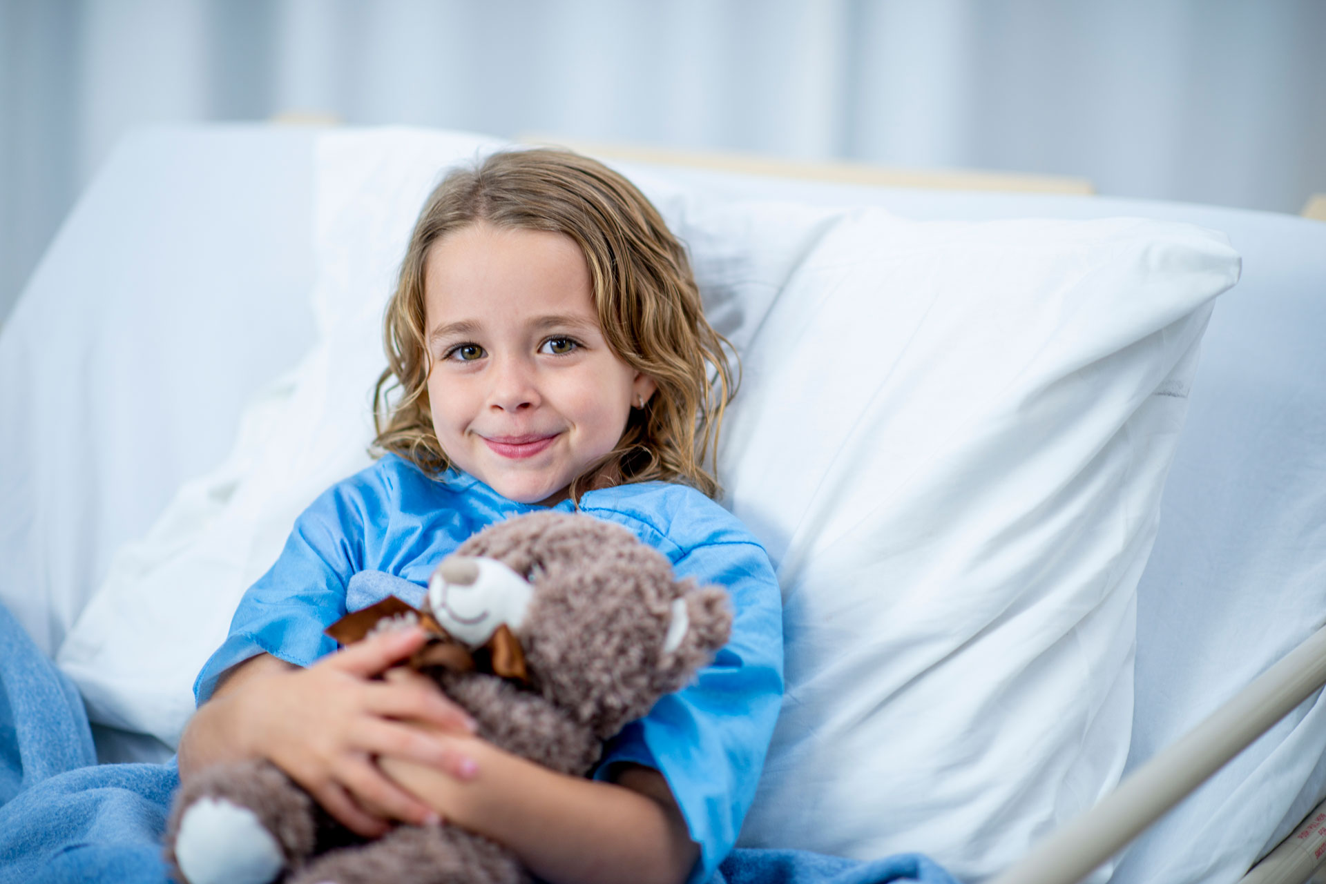 Young girl with teddy bear in hospital