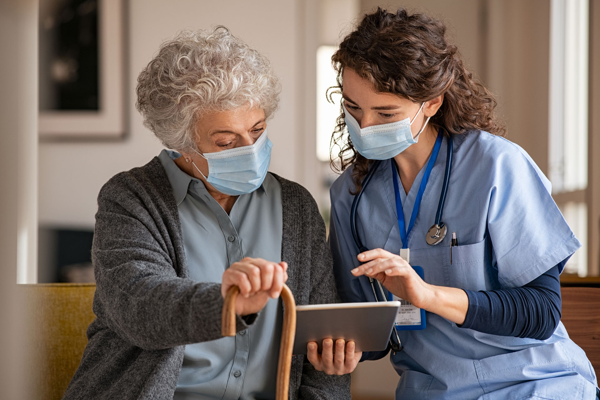 Young doctor and senior woman going through medical record on digital tablet during home visit wearing face protective mask.